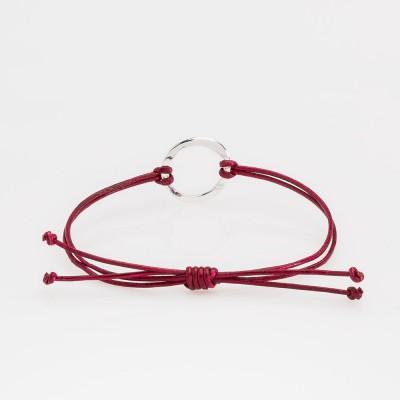 Vista frontal de una pulsera Nelumbo de la colección link con nudos de cuero rojo y círculo de plata.
